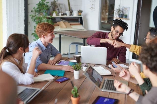 Skupina smějících se mladých lidí sedících kolem stolu s počítači-pracovní porada